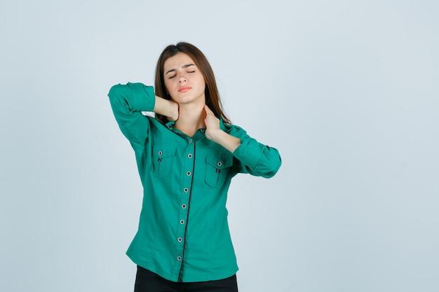 Mooie jonge dame die nekpijn voelt in een groen shirt en ongemakkelijk kijkt, vooraanzicht.