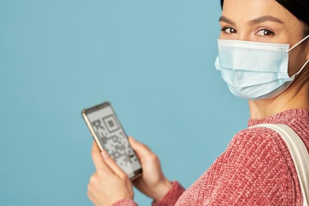 Mooie jonge dame die smartphone gebruikt en een medisch wegwerpmasker draagt