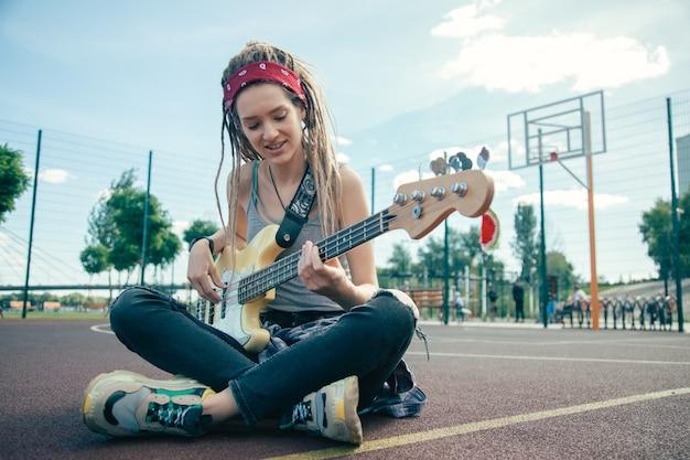 Mooie jonge dame die vrijetijdskleding draagt en er ontspannen uitziet tijdens het spelen van de gitaar op het sportveld