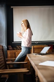 Mooie jonge dame die zich in het koffiewerk bevinden met laptop.