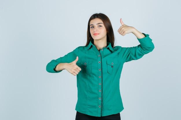 Mooie jonge dame dubbele duimen opdagen in groen shirt en op zoek trots, vooraanzicht.