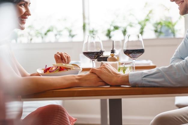 Mooie jonge dame en man hand in hand en glimlachend zittend aan tafel met heerlijk eten en wijn