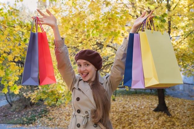 Mooie jonge dame geniet van goed winkelen. veelkleurige boodschappentassen. verkoop herfst.