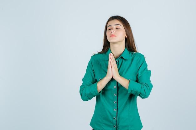 Mooie jonge dame hand in hand in gebed gebaar in groen shirt en op zoek hoopvol, vooraanzicht.