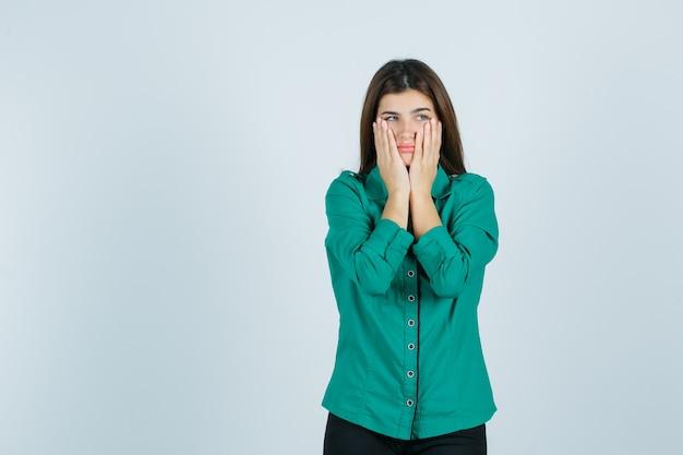 Mooie jonge dame hand in hand op de wangen in een groen shirt en neergeslagen, vooraanzicht kijken.