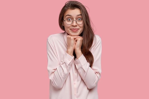 Mooie jonge dame houdt de handen onder de kin, heeft ogen vol geluk, lang donker haar, gekleed in een stijlvol overhemd