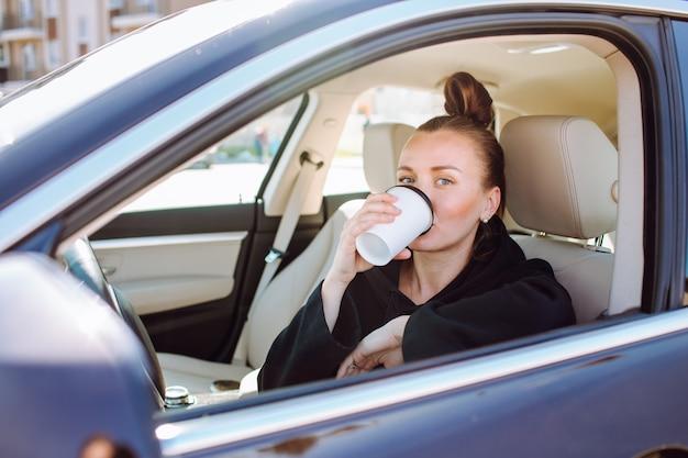 Mooie jonge dame in auto en koffie drinken