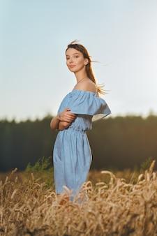Mooie jonge dame in een tarweveld bij zonsondergang