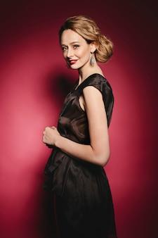 Mooie jonge dame in elegante zwarte jurk met avond make-up en oorbellen poseren terug met gesloten ogen op roze achtergrond, modieuze glamour foto