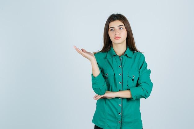 Mooie jonge dame in groen overhemd die palm opzij spreidt en depressief, vooraanzicht kijkt.