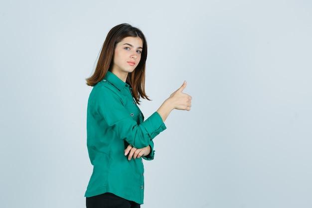 Mooie jonge dame in groen overhemd duim opdagen en zelfverzekerd op zoek.