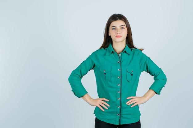 Mooie jonge dame in groen overhemd hand in hand op de taille en op zoek naar zelfverzekerd, vooraanzicht.