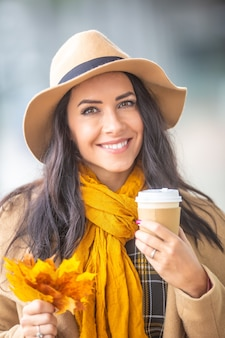Mooie jonge dame in hoed met herfstbladeren en koffie afhaalmaaltijden mok in haar handen.