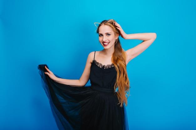 Mooie jonge dame in mooie zwarte pluizige jurk poseren op feestje, glimlachend. ze heeft lang golvend haar en draagt een diadeem met kattenoren met kristallen.