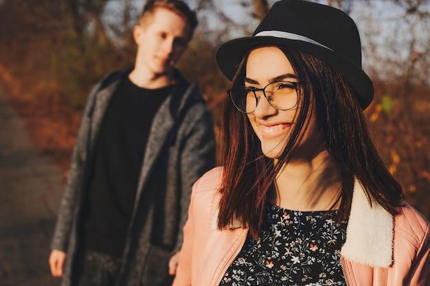Mooie jonge dame in stijlvolle bril en hoed glimlachend en weg op zoek tijdens het wandelen met vriendje in de herfst natuur. vrolijke vrouw wandelen met vriendje in platteland