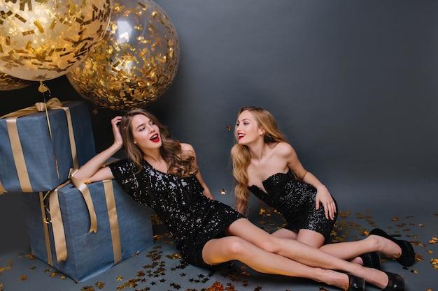 Mooie jonge dame in zwarte jurk viert verjaardag met beste vriend. spectaculaire langharige meisje in elegante schoenen poseren op de vloer met ballonnen en cadeautjes tijdens fotoshoot met zus.