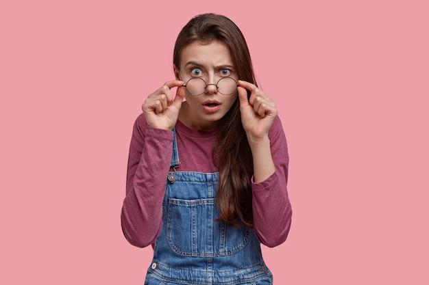 Mooie jonge dame kijkt nauwgezet door bril, houdt de handen op de rand, opent mond van verrassing