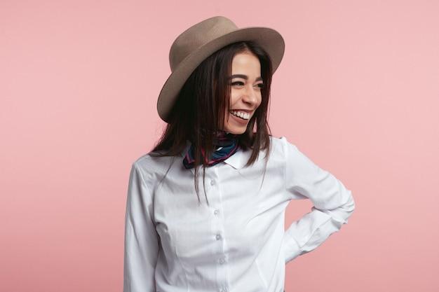Mooie jonge dame lacht vrolijk over roze studio