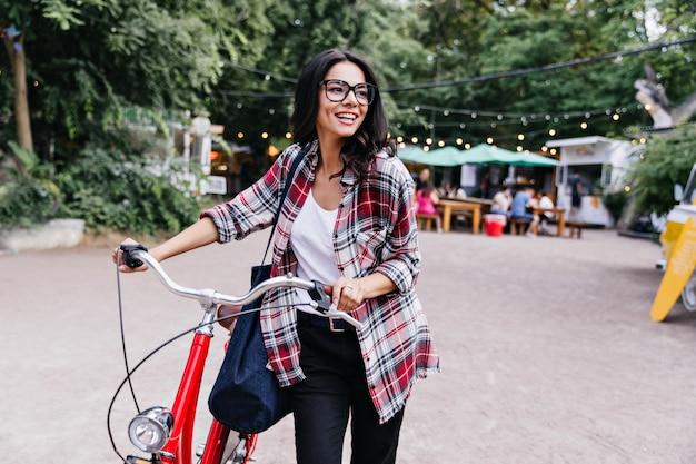 Mooie jonge dame met donker haar staande op straat met fiets. foto van geïnteresseerd brunette meisje in zwarte broek met plezier in weekend.