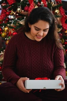 Mooie jonge dame met een kerstcadeau