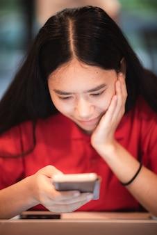 Mooie jonge dame met een rood t-shirt glimlachend, met behulp van de telefoon voor online werk, een spel spelen op de mobiele telefoon, lifestyle gadget concept, binnen thuis, thuis werken, technologie.