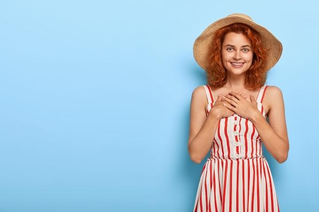 Mooie jonge dame met gemberhaar poseren in zomerjurk en strooien hoed