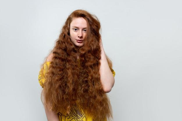 Mooie jonge dame met lang rood haar in gele jurk op grijs