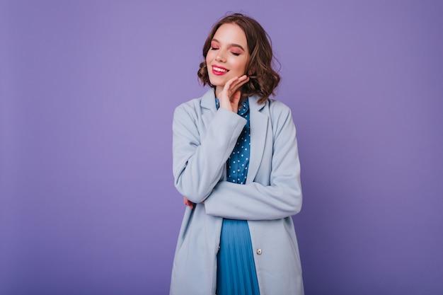 Mooie jonge dame met lichte make-up poseren in herfst kleding. binnenfoto van schattig krullend meisje in blauwe jas geïsoleerd op paarse muur.