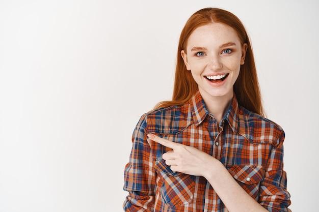 Mooie jonge dame met natuurlijk gemberhaar, glimlachend en gelukkig kijkend, wijzende vinger naar links naar promobanner, witte muur