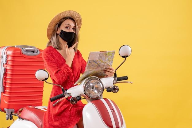 Mooie jonge dame met zwart masker op de kaart van de bromfiets