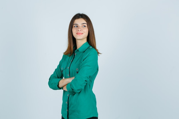 Mooie jonge dame permanent met gekruiste armen terwijl wegkijken in groen shirt en op zoek vrolijk, vooraanzicht.