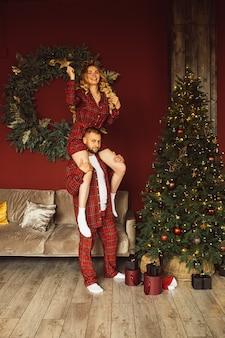 Mooie jonge dame zittend op de schouders van haar man en kerstboom versieren Premium Foto
