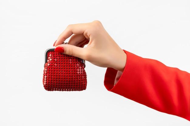 Mooie jonge dames hand met rode manicure houdt portemonnee op grijs wallet