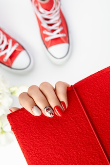 Mooie jonge dames hand met rode manicure op grijs manicure