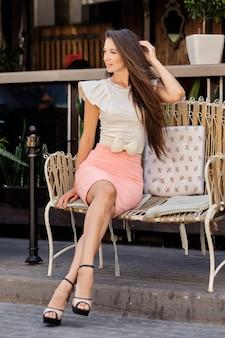 Mooie jonge damezitting op metaalbank dichtbij koffieterras