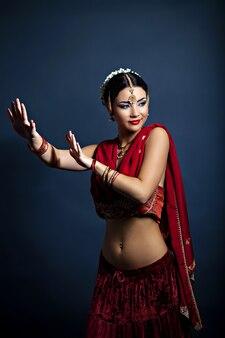 Mooie jonge dansende vrouw in traditionele indiase kleding