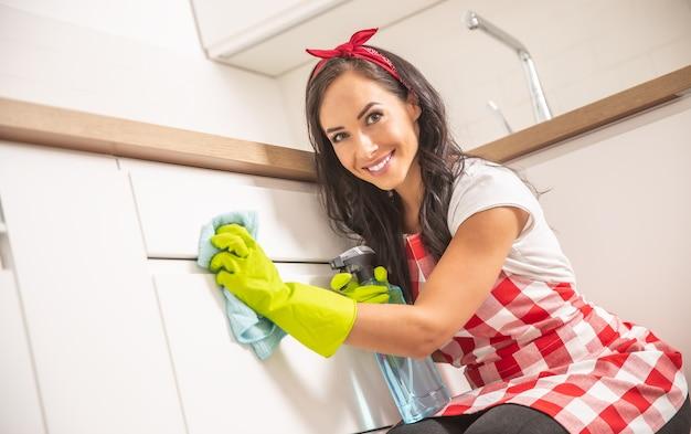Mooie jonge dienstmeid in schort die de deur van de witte keukenkast schoonmaakt met een doek en wasmiddel in gele rubberen handschoenen.