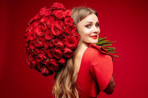 Mooie jonge donkerbruine dame in rood met bos van rode rozen op schouder