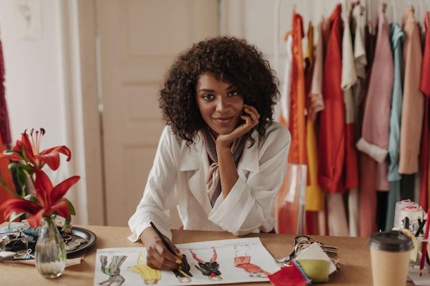 Mooie jonge donkerbruine, krullende brunette vrouw in witte blouse kijkt naar voren, leunt op tafel en ontwerpt stijlvolle kleding