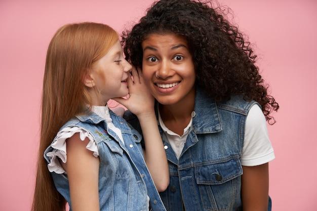 Mooie jonge donkerbruine krullende brunette vrouw met neuspiercing die verwonderd kijkt en wenkbrauwen verrast terwijl ze luistert naar geheime verhalen op roze