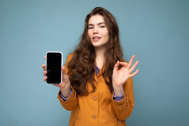 Mooie jonge donkerbruine vrouw die oranje jasje draagt dat over blauwe achtergrond in hand houdt en mobiel toont