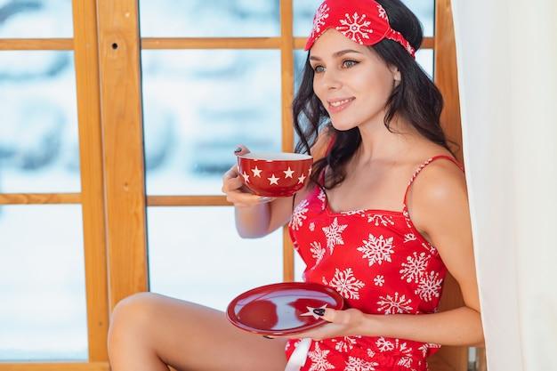 Mooie jonge donkerbruine vrouw die rode pyjama draagt die thuis door het venster zitten