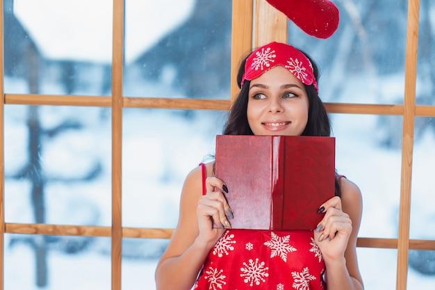 Mooie jonge donkerbruine vrouw die rode pyjama draagt en door het venster leest