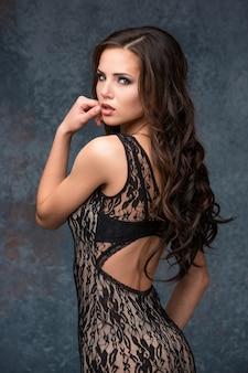 Mooie jonge donkerbruine vrouw met haar haar het stellen in een maaswerkkleding.