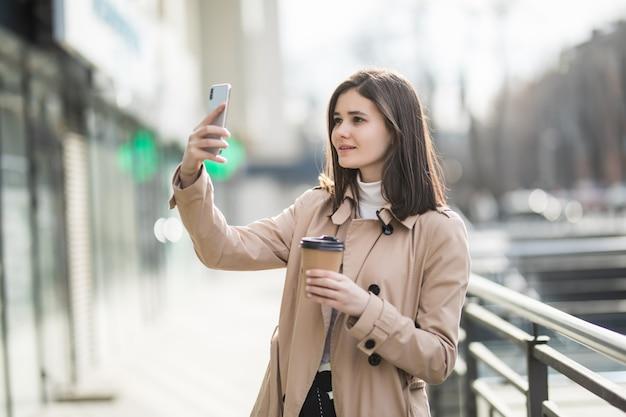Mooie jonge donkerbruine vrouw met meeneemkoffie die selfie nemen