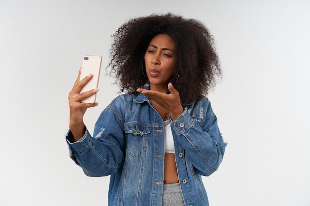 Mooie jonge, donkere dame met casual kapsel die mobiele telefoon in de hand houdt, handpalm opheft en luchtkus blaast naar camera, geïsoleerd over witte muur