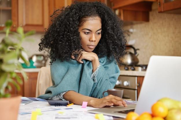 Mooie jonge donkere vrouw met afro-kapsel die omslag draagt ?? die hand op touchpad houdt