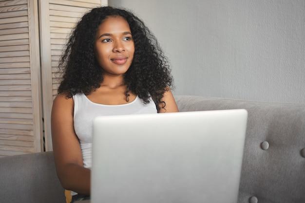 Mooie jonge donkere vrouw met afro kapsel surfen op websites met generieke draagbare computer terwijl u ontspant thuis op de bank. vrouwelijke freelancer van gemengd ras die op afstand aan laptop werkt