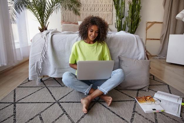 Mooie jonge donkere vrouw met bruin krullend haar zittend op tapijt in de slaapkamer met laptop op haar benen, het dragen van vrijetijdskleding, positieve stemming