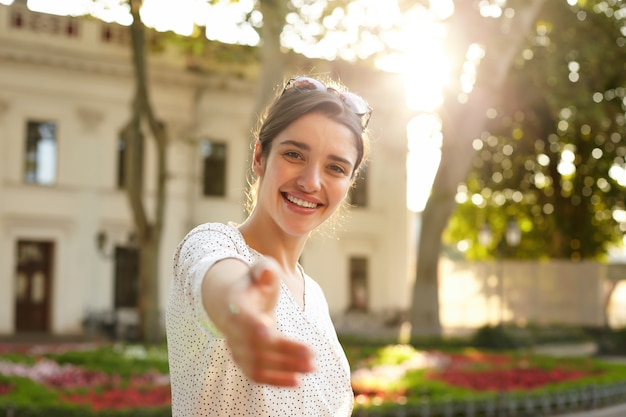 Mooie jonge donkerharige brunette bruinogige vrouw hand opsteken in welkom gebaar terwijl ze gelukkig kijkt en grof lacht, zonnebril op haar hoofd draagt